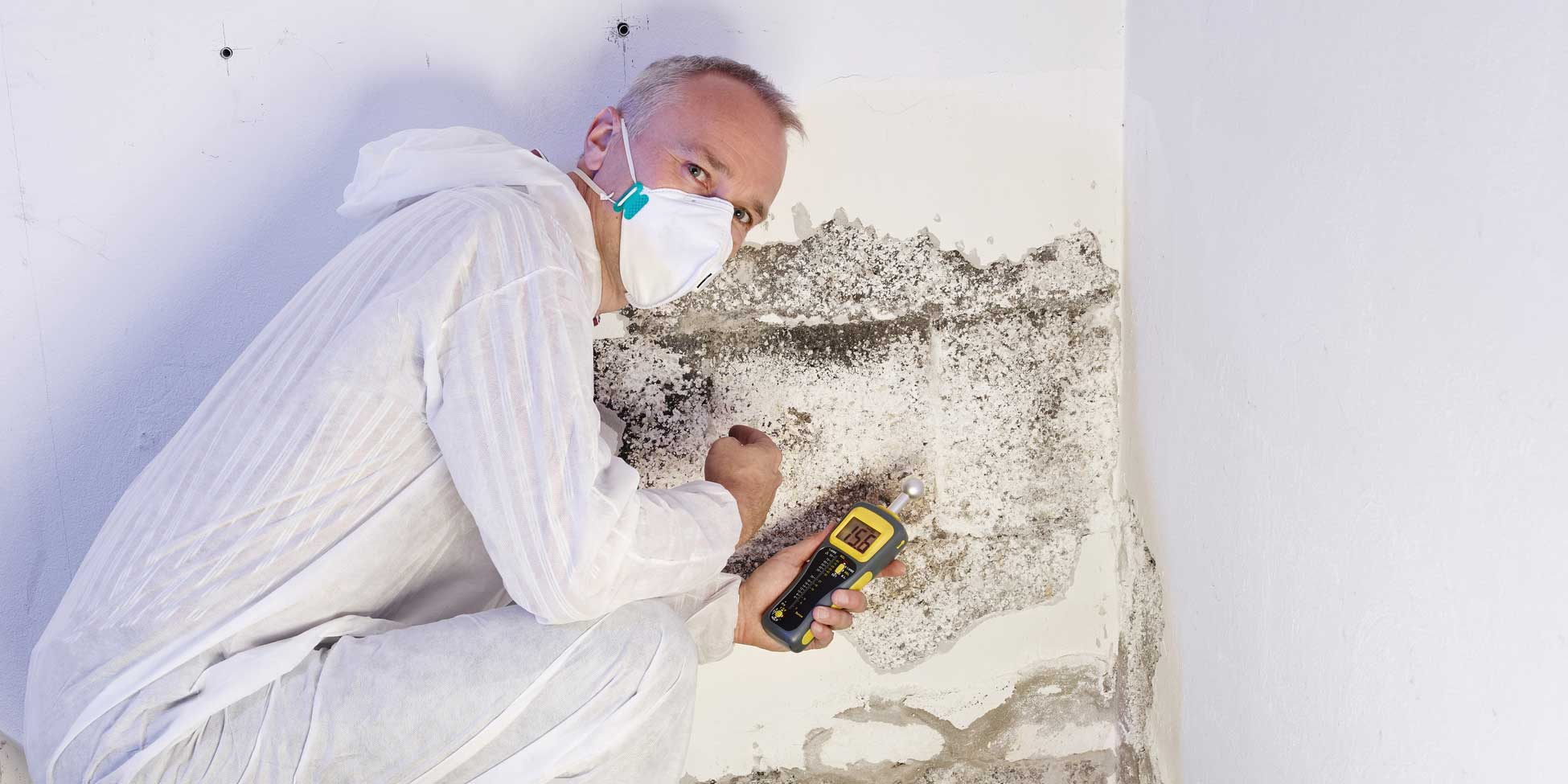 Mann vor schimmeliger Wand