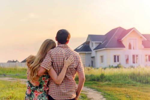 Vor einem weißen Haus steht ein junges Paar, das sich umarmt.